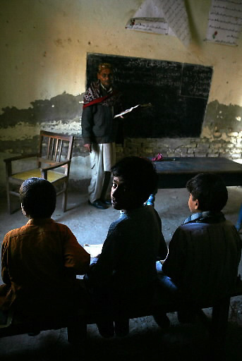 A child looks over his shoulder during a lesson at a primary school in the Khairo Dero village in Larkana, Pakistan, on Wednesday, Jan. 23, 2008. Pakistan is seeking to sustain growth in a country where the government estimates a fourth of the population lives in poverty, or on less than a dollar a day.