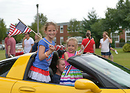 Wantagh, New York, USA. July 4, 2015. Two smiling young girls, holding an American Flag and wearing a red white and blue sash, stand as they ride in a yellow sports car in the Wantagh July 4th Parade, a long-time Independence Day tradition on Long Island.