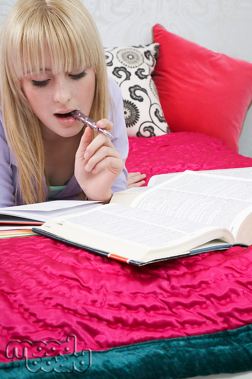Teenage girl (16-17) lying on bed doing homework