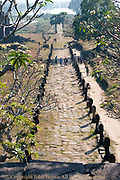 Tourists are walking on a stone pathway leading to a steep set of stairs at the ruins of ancient and historic Angkor era Wat Phu, built by the Khmers, in Champasak, Laos. Wat Phu was granted UNESCO World Heritage status in 2001.