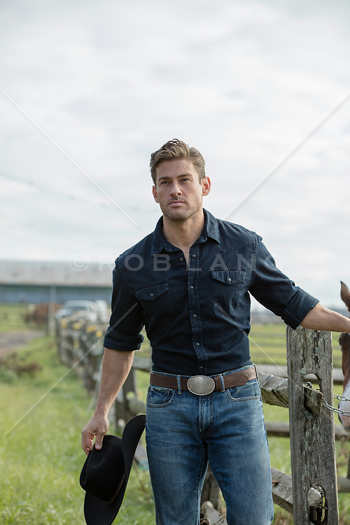 handsome cowboy holding his cowboy hat on a ranch