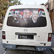 Keeping it in the family: Bassel al-Assad (left) who died in 1994 was groomed to take over presidency from his father, former president Hafez al-Assad (centre). His brothers death meat the presidency fell to Bashar al-Assad in 2000 (right). Rear window decal on a van in Damascus.
