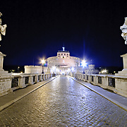 Castel Sant'Angelo, Rome, from across the cobblestone bridge at night.