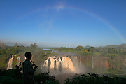 TISSISAT, GOJJAM/ETHIOPIA..Rainbow over the waterfalls of the Blue Nile, approyimately 35kms downriver from its origin at Bahar Dar/Lake Tana. Litle boy playing a traditional flute..(Photo by Heimo Aga)