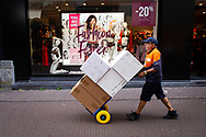 Den Haag. Pakketbezorger loopt langs lingeriewinkel. Foto: Gerrit de Heus. The Netherlands. The Hague. Parcel Delivery. Photo: Gerrit de Heus
