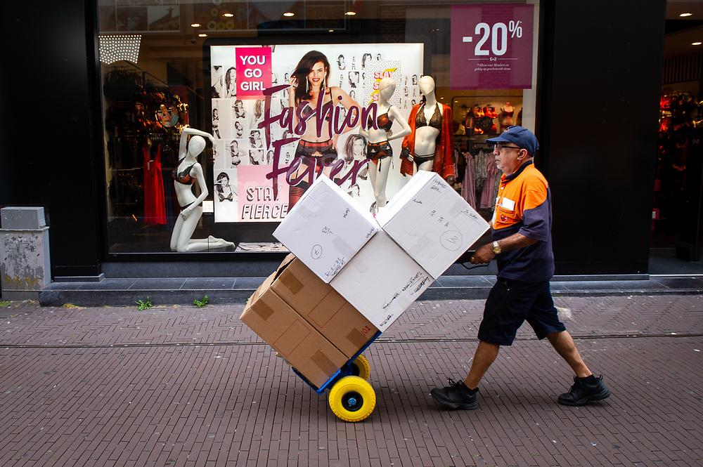 Den Haag. Pakketbezorger loopt langs lingeriewinkel. Foto: Gerrit de Heus. The Netherlands. The Hague. Parcel Delivery. Photo: Gerrit de Heus