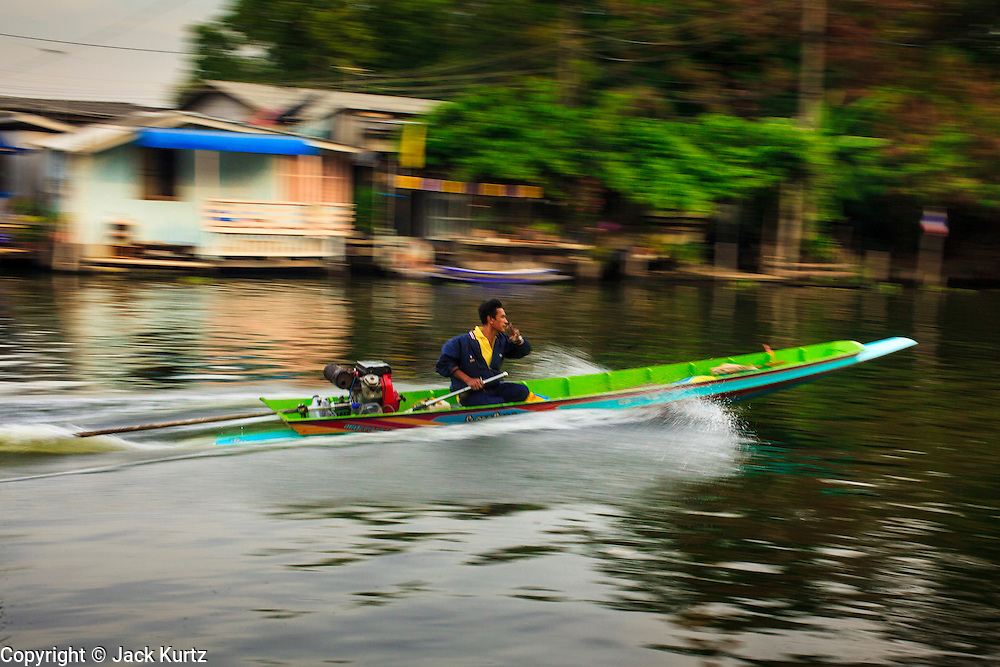 04 JANUARY 2012 - BANGKOK, THAILAND:   A small boat speeds up Khlong Phra Khanong past Wat Mahabut in eastern Bangkok. The temple was built in 1762 and predates the founding of the city of Bangkok. Just a few minutes from downtown Bangkok, the neighborhoods around Wat Mahabut are interlaced with canals and still resemble the Bangkok of 60 years ago. Wat Mahabut is a large temple off Sukhumvit Soi 77. The temple is the site of many shrines to Thai ghosts. Many fortune tellers also work on the temple's grounds.  PHOTO BY JACK KURTZ