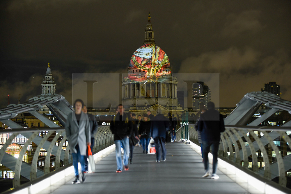 """© Licensed to London News Pictures. 27/11/2019. LONDON, UK.  William Blake's final masterpiece is projected onto the iconic dome of St Paul's Cathedral, in celebration of the artist's birthday.  The illustration of """"Ancient of Days"""", 1827, can be seen until 1 December as part of a collaboration between St Paul's Cathedral and Tate Britain, which is currently staging the UK's largest survey of work for a generation.  Photo credit: Stephen Chung/LNP"""