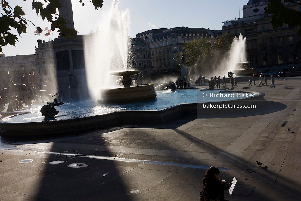 Wide backlit landscape of Trafalgar Square and the spray of its fountains.