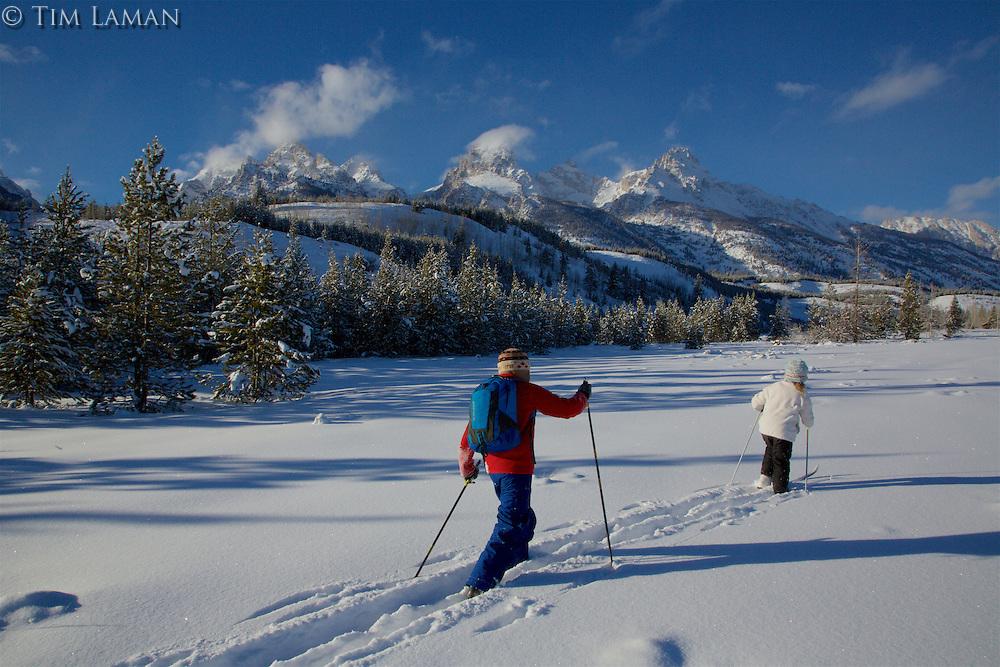 Russell Laman (age 12) and Jessica Laman (age 9)  cross-country skiing below the Teton Range.<br />Grand Teton National Park, Wyoming