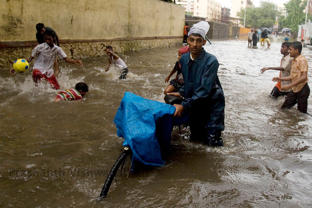 A daily commuter pushes his cycle through a flooded road in Mumbai, India, on Friday July 1, 2008. Photographer:  Prashanth Vishwanathan/Bloomberg News