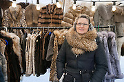 Portrait of a mature woman standing in front of fur stall