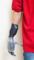 Cropped image of man with prosthetic hand over gray background