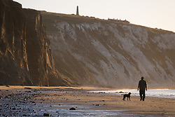 © Licensed to London News Pictures. 23/09/2016. Sandown, Isle of Wight, UK.  A dog walker on the beach at Yaverland beach on the Isle of Wight this morning, 23rd September 2016. The day has started cool, but fine and sunny. It will become a little cloudier and breezier later in the South East of England. Photo credit: Rob Arnold/LNP