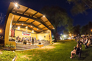 Port Washington, New York, USA. 26th June 2015. At night concert, the Swingtime Big Band performs music at John Philips Sousa Memorial Band Shell, at Sunset Park along Manhasset Bay in the North Shore village on Long Island Gold Coast. The audience sits on chairs and benches on the lawn of the public park.