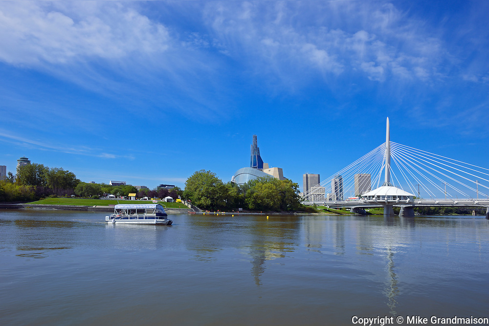Winnipeg skyline with Canadian Museum for Human Rights and Esplanade Riel bridge with tour boat on the Red River<br /> Winnipeg<br /> Manitoba<br /> Canada