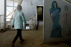 October 5, 2016 - Athens, Greece - A woman walks next to a graffiti at the sports facilities at Helliniko olympic complex in Athens, Greece on October 5, 2016.Almost 2,500 migrants and refugees, mainly Afghani, are housed at the former Athens airport site, and to an olympic complex used in the 2004 Olympics. In total 60.736 refugees and other migrants are stranded in Greece. (Credit Image: © Panayiotis Tzamaros/NurPhoto via ZUMA Press)