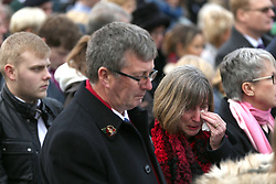 People observe a two minute silence during a service of Remembrance at the National Memorial Arboretum in Staffordshire.
