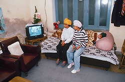 Young boys sitting on bed watching television,