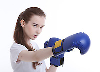 Portrait of young Caucasian woman with boxing gloves against white background