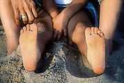 Sandy feet of young child sitting with mother on the beach.
