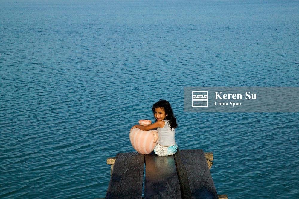 Little girl carrying jar by Lago Peten Itza, Remate, Guatemala