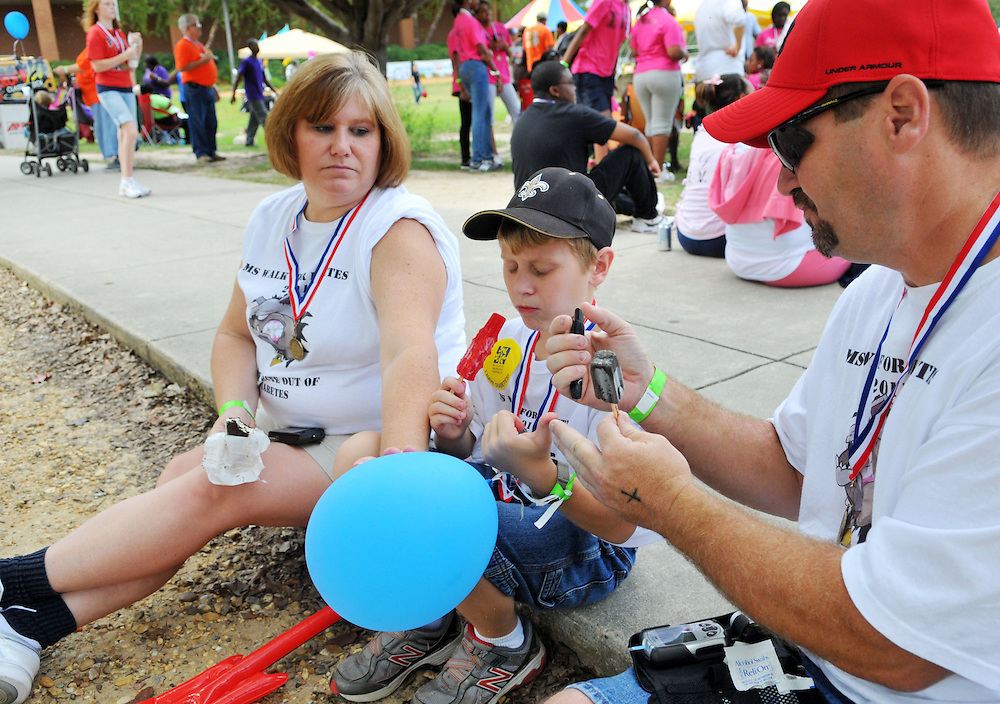 "Jerry and Sharon Bilbo check their son Jared's blood sugar after the Mississippi Walk for Diabetes event at Pride Field Sunday afternoon. Sunday was the one year anniversary of Jared's diagnostic as a diabetic. ""We're still crunching numbers, but it's getting better,"" said his mother.  Bryant Hawkins/ Hattiesburg American"