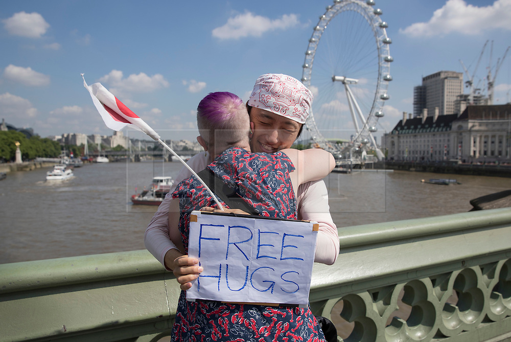 © Licensed to London News Pictures. 25/05/2017. London, UK. A Japanese man stands on Westminster Bridge with a sign offering 'Free hugs' following a terrorist attack in Manchester, northern England, earlier this week.   23 people were killed an dozens more injured when Salman Abedi denonated a suicide bomb at an Ariana Grande concert. Photo credit: Peter Macdiarmid/LNP