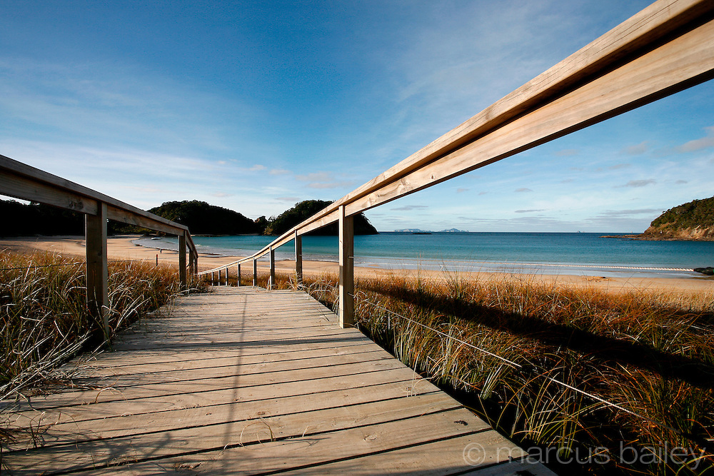 wooden walkway leads across the dune grass down to the golden sand and blue sea at matapouri, northland, new zealand