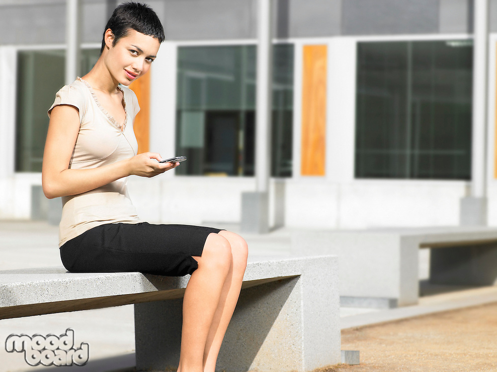 Young woman sitting in plaza sending text message portrait