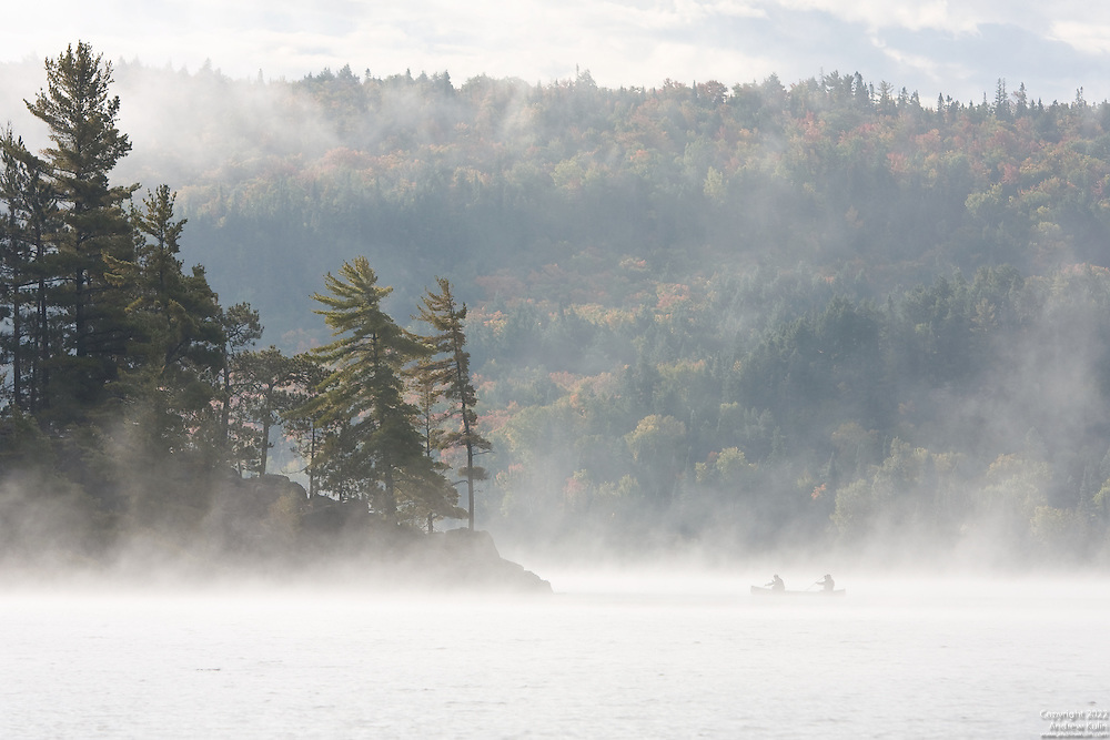 Two early morning canoeists paddling in the early morning mist on the Lake of Two Rivers in Algonquin Provincial Park.<br />