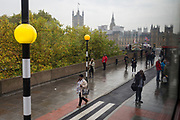 Pedestrians and the new cycle lane zebra crossing, across the Thames river from the Houses of Parliament on Westminster Bridge, on 19th October 2017, in London, England.