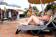 Woman lying on a deckchair poolside watching young girls while they change their bathing suits.