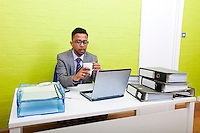 Portrait of Indian Businessman holding mug and working on his laptop computer at his desk