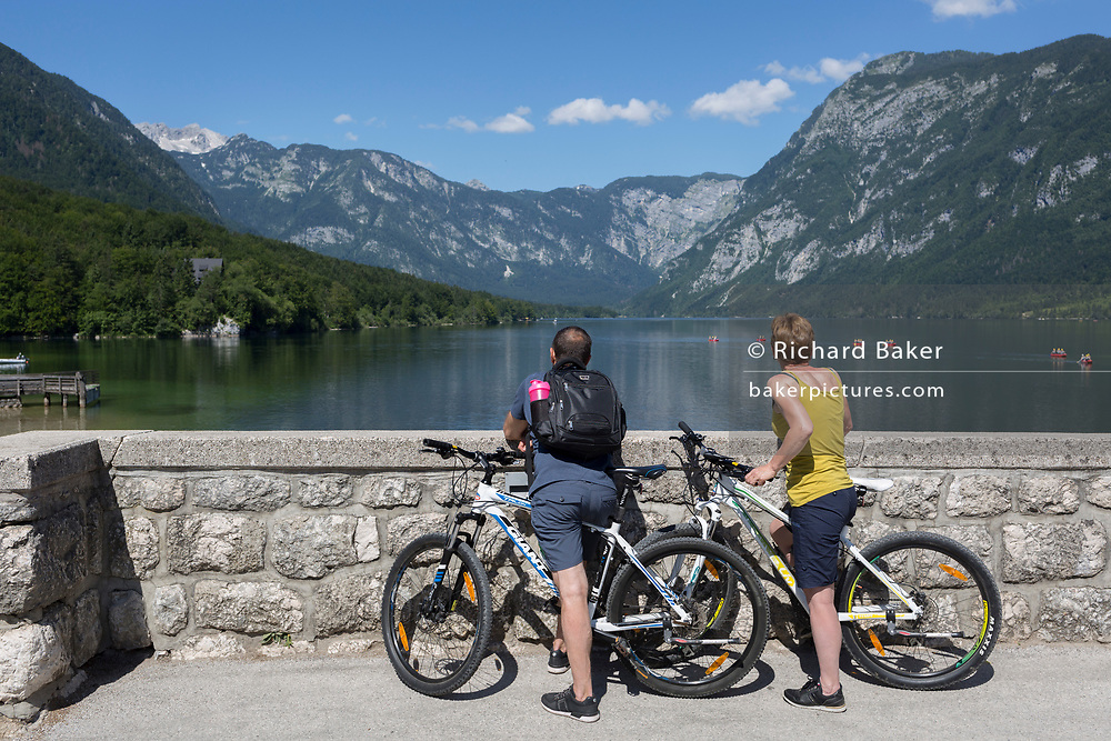 Cyclists admire the view from the bridge at Ribcev Laz and out into Lake Bohinj, on 19th June, in Lake Bohinj, Sovenia