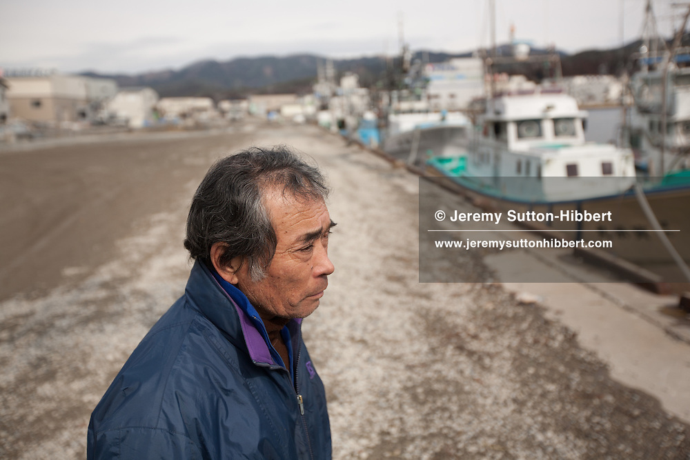 Wataru Sato, aged 63yrs, stands by the waters edge in Kesennuma harbour as nearby divers and ground crews of the Japanese coast guard search underwater in the harbour for the bodies of victims of the March 11th 2011 tsunami, in Kesennuma, Japan, on Tuesday 14th February 2012..Sato's sister, Kiyako KOMATSU, 68, died in the tsunami, along with her husband and one of their sons. Their other son survived. They were on their way to a wake for one of her husband's relatives when they got caught up in the waves, according to Sato. He said that eight of his cousins, who lived in one of the worst-hit parts of Kesennuma, also died.