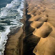 A wall of sand dunes outside of Swakopmund lines the coast of Namibia. For decades, the Skeleton Coast, buffeted by impenetrable fog, perilous cross currents and treacherous reefs, has been a graveyard for ships. July 16, 2008. Photo by Evelyn Hockstein for The New York Times.