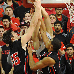 Connecticut Huskies forward Tyler Olander (10), Rutgers Scarlet Knights forward Gilvydas Biruta (55) and guard/forward Derrick Randall (15) battle for a rebound during Rutgers' 67-60 upset victory over #8 UConn in NCAA Big East Basketball action at the Louis Brown Athletic Center in Piscataway, N.J. on Jan 7, 2012.