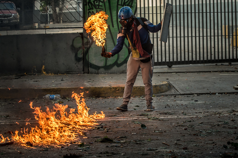 CARACAS, VENEZUELA - JULY 26, 2017: Members of La Resistencia throw molotov cocktails at soldiers, who responded with tear gas, rubber bullets and buckshot, during an anti-government protest to demand that the National Constituent Assembly election scheduled for Sunday, July 30th be cancelled. The political opposition called for a 48 hour national strike on July 26th and 27th, and for their supporters to close businesses, not go to work, and instead create barricades to block off their streets.  Opposition controlled areas of the country were completely shut down.  The strike was called as part of the opposition's civil resistance movement - that began on April 1st, to protest against the Socialist government's attempt to elect a new assembly that will have the power to re-write the constitution, and their opposition to the Socialist's continued threats to Venezuelan Democracy.  PHOTO: Meridith Kohut for The New York Times