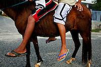 Two boys travel by horseback in Playa Esperanza, Vieques, Puerto Rico.