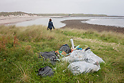 A walker passes a pile of assorted plastic materials awaiting removal from the coastal landscape, having been collected by volunteers from a beach on Holy Island, on 27th September 2017, on Lindisfarne Island, Northumberland, England. The amount of rubbish found dumped on UK beaches rose by a third last year, according to a new report. More than 8,000 plastic bottles were collected by the Marine Conservation Society's annual beach clean-up at seaside locations from Orkney to the Channel Islands on one weekend in September 2016. The Holy Island of Lindisfarne, also known simply as Holy Island, is an island off the northeast coast of England. Holy Island has a recorded history from the 6th century AD; it was an important centre of Celtic and Anglo-saxon Christianity. After the Viking invasions and the Norman conquest of England, a priory was reestablished.