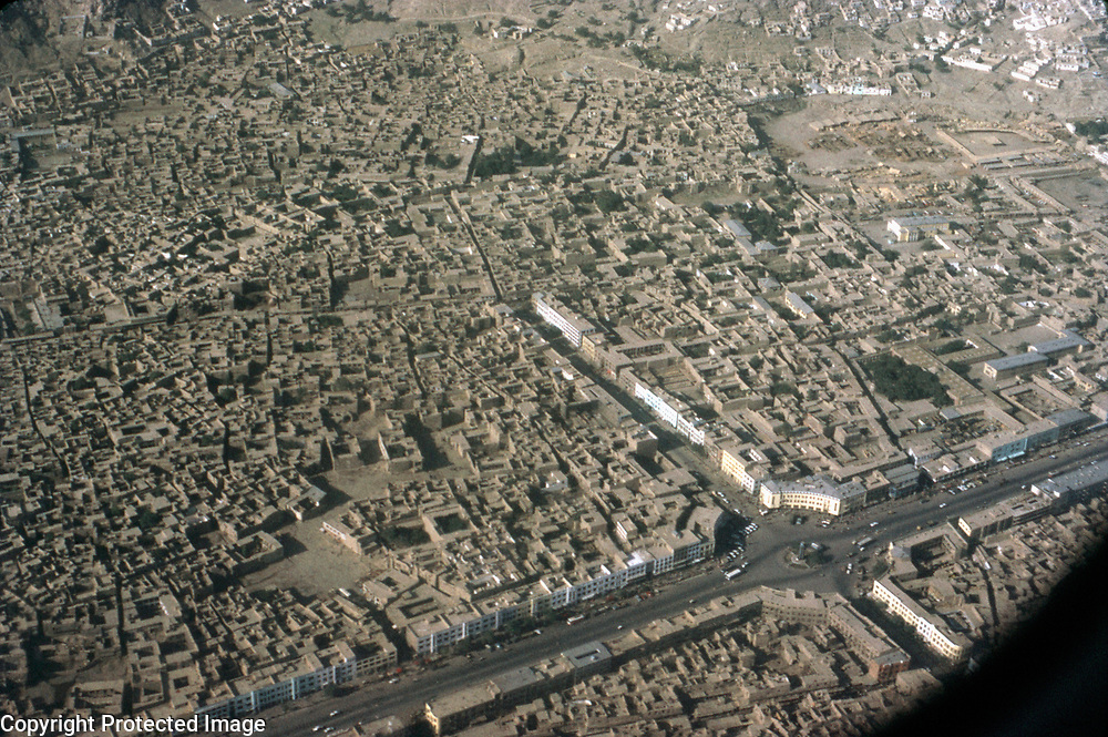 5 July 1975<br /> Shor Bazaar. Midway along Jadi Maiwand a broad street lined with whitewashed buildings runs toward the mountains. At its end it meets the entrance to the ancient Shor Bazaar running in a straight line parallel to Jadi Maiwand along the outside walls of the citadel until it ends at the main road leading out of the city to the east. Along this unpaved road filled with mechanized and animal transport all manner of merchandize is available, but exotic spices sold n the vicinity of the Hindu and Sikh temples located here are particularly sought after. Paper kites for kite-flying competition from Shor Bazaar were also a valued buy.