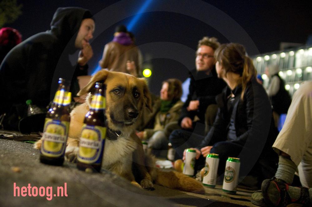 festival bezoekers van het aki festifal op het stationsplein te enschede samen met een hond en flesjes en blikjes bier