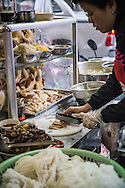 Vietnamese woman slices up chicken meat at a bun thang street restaurant stall, Hanoi, Vietnam, Southeast Asia