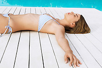 Young Woman Sunbathing on deck by swimming pool side view