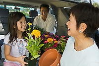 family loading flowers into back of SUV close up