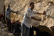 Egyptian men desperately point to areas where they believe their family members are trapped as others dig by hand September 06, 2008 following a giant rockslide that killed at least 64, and trapped hundreds more in the Manshiyet Nasr shantytown on the eastern edge of the capital, Cairo.