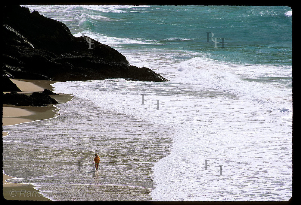 Lone woman wades along Coumeenole Beach near Dunmore Head on a September afternoon; Dingle Peninsula, Ireland.