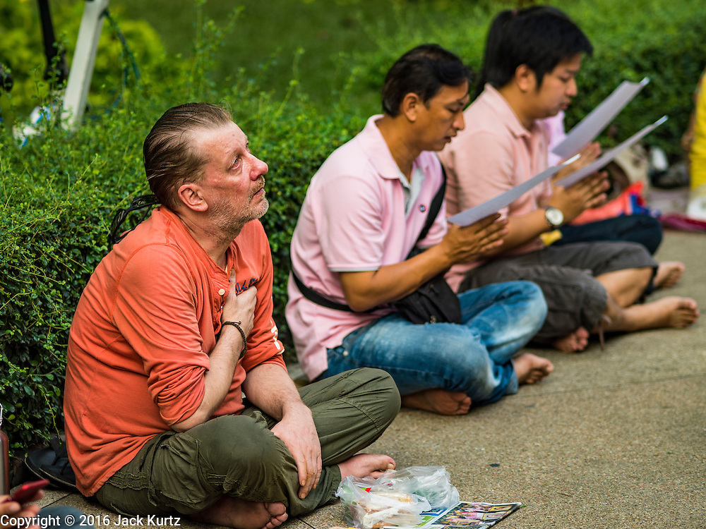 13 OCTOBER 2016 - BANGKOK, THAILAND:   A foreign man joins Thais in praying for Bhumibol Adulyadej, the King of Thailand, at Siriraj Hospital Thursday morning before the King's death was announced. Thousands of people came to the hospital to pray for the beloved monarch. Bhumibol Adulyadej, the King of Thailand, died at Siriraj Hospital in Bangkok Wednesday, October 13, 2016. Bhumibol Adulyadej, 5 December 1927 – 13 October 2016, was the ninth monarch of Thailand from the Chakri Dynasty and is known as Rama IX. He became King on June 9, 1946 and served as King of Thailand for 70 years, 126 days. He was, at the time of his death, the world's longest-serving head of state and the longest-reigning monarch in Thai history.     PHOTO BY JACK KURTZ