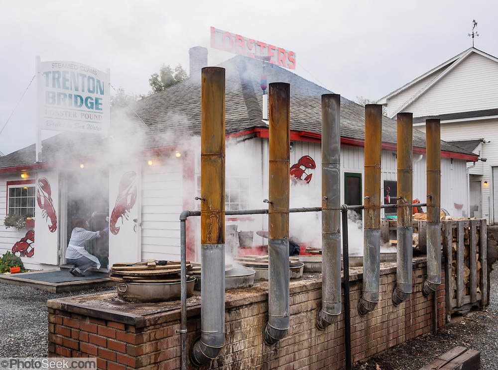 Outdoor wood-fired stoves boil lobsters in fresh, clean seawater at Trenton Bridge Lobster Pound, in Trenton, Maine, USA. Trenton Bridge Lobster Pound serves delicious seafood, highly recommended. Address: 1237 Bar Harbor Rd, Trenton, ME 04605. Phone (207) 667-2977.